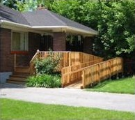brick bungalow style-home with a wooden ramp up to the front porch