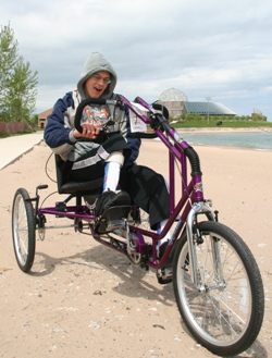 Teen in a sweatshirt rides a purple cycle that has been adapted with three wheels, larger handlebars, and pedal plates with straps