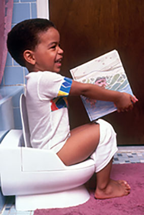 child sitting on a child's potty smiling and holding a book