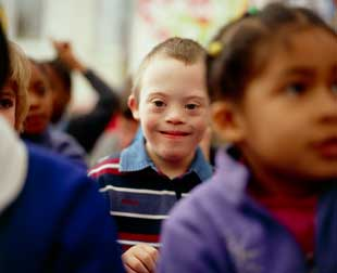 Six-year-old boy with Down syndrome (centre), with fellow pupils at a mainstream school. Down's syndrome is a chromosomal abnormality resulting in mental handicap and a characteristic physical appearance.
