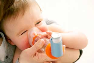 A baby using a spacer with an inhaler.