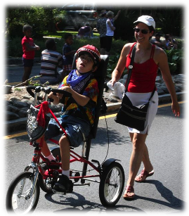 Mother following son who is riding an adaptive tricycle